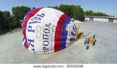 RUSSIA, MOSCOW - MAY 18, 2014: Fire flame goes during inflation of air balloon on square of park Sokolniki at spring sunny day. Aerial view