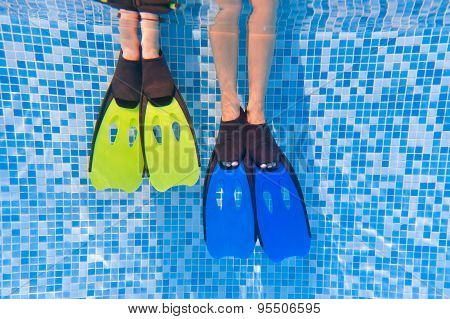 Underwater kid's legs in fins in swimming pool