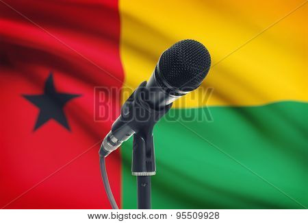 Microphone On Stand With National Flag On Background - Guinea-bissau