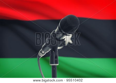 Microphone On Stand With National Flag On Background - Libya