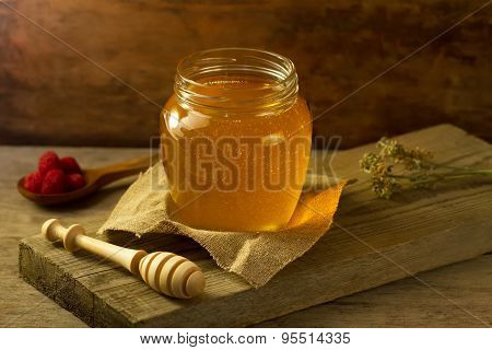 Glass Jar Of Honey With A Drizzler, Raspberries, Jute Fabric, Dried Flowers On Wooden Background