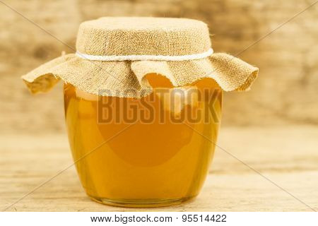Glass Jar Of Honey Closed Jute Cloth On Wooden Background
