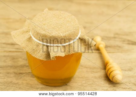 Glass Jar Of Honey Closed Jute Cloth Drizzler On Wooden Background