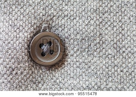 Close - up brown plastic button on grey shirt