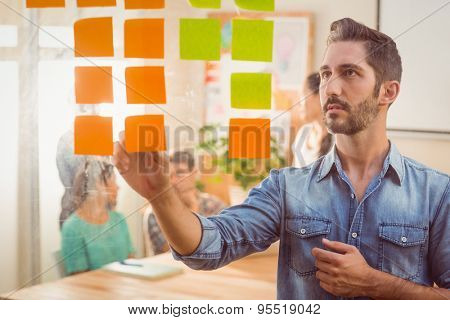 Concentrated businessman looking post its on the wall in the office