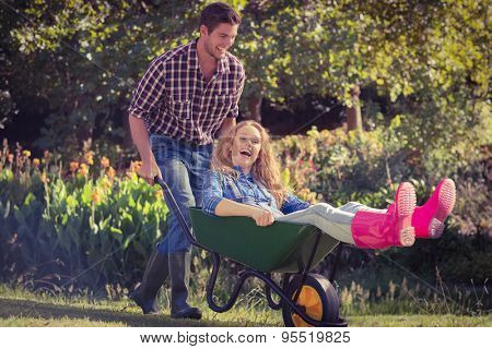 Man pushing his girlfriend in a wheelbarrow on a sunny day