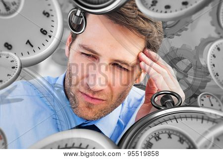 Stressed businessman holding his head against grey vignette