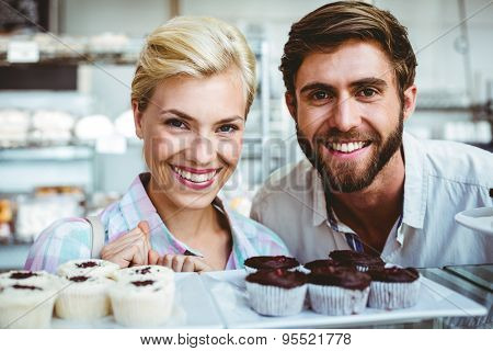 Cute couple on a date looking at the camera at the bakery