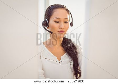 Young call centre representative using headset in office