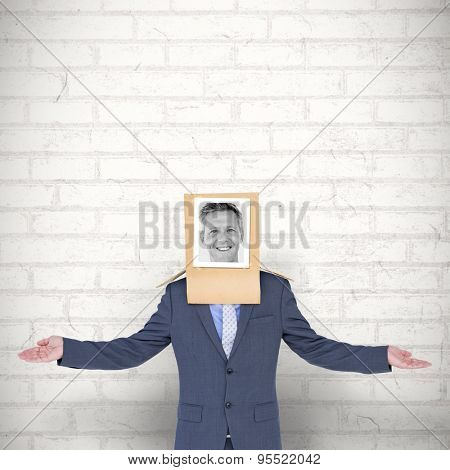 Businessman with photo box on head against white wall