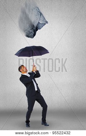 Businessman sheltering under black umbrella against grey wall
