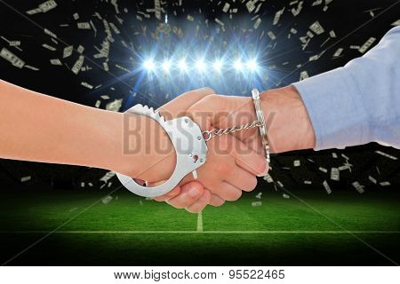 Handcuffed business people shaking hands against football pitch under spotlights