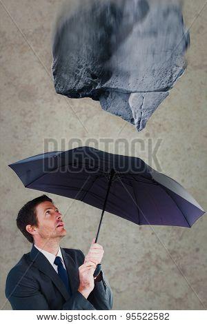 Businessman sheltering under black umbrella against grey room