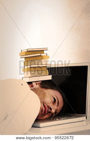 Businessman resting head on laptop keyboard against grey room