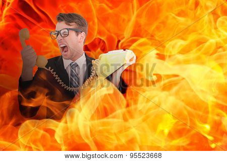 Geeky businessman shouting at telephone against fire