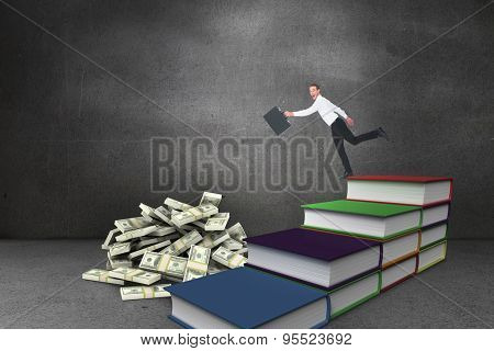 Happy businessman leaping with his briefcase against steps made from books in grey room
