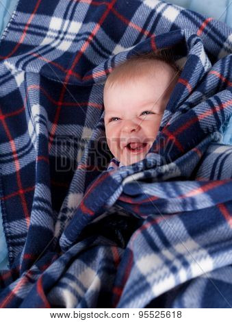 Cute baby boy hiding in plaid