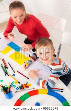 Smiling boy drawing picture with his mother