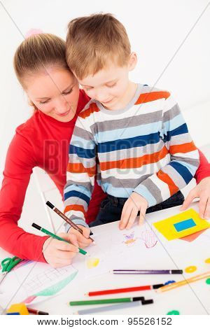 Mother teaching her little boy to draw