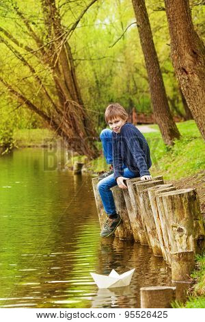 Boy sitting with bended knee near the pond