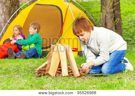 Boy prepares bonfire in forest with other children