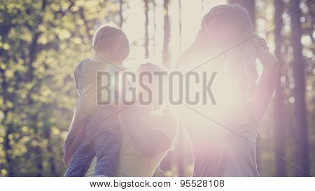 Concept Of Family Values And Happiness - Young Family With Two Kids In A Forested Area
