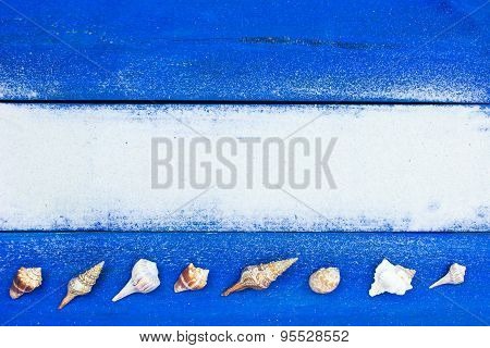 Beach sign with seashells and sand