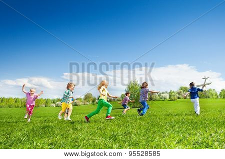 Boy with airplane toy and kids row running after