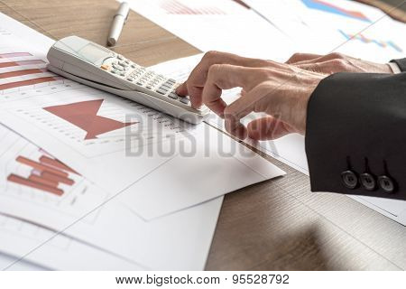Business Adviser Or Banker Making Calculations On A Desktop Calculator