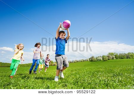 Boy holding rocket carton toy and children running