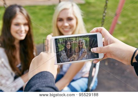 happy memories of girl friends being captured by mobile cell phone camera outdoors