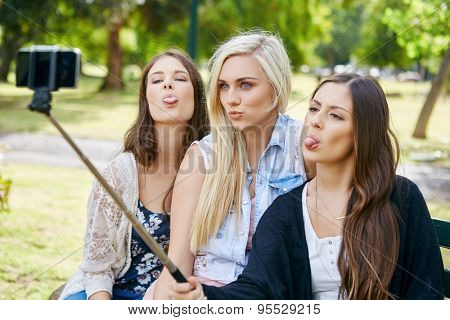 young happy girl friends sitting on park bench taking selflie photos with mobile cell phone on stick
