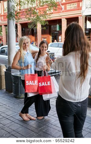 capturing memories with mobile phone camera of fun weekend shopping teen girl friends with bags on city sidewalk