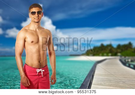 Man on beach with jetty at Maldives. Collage.