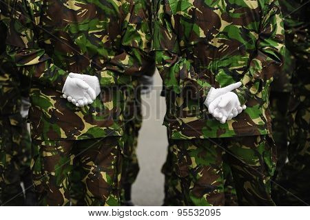 Soldiers In Camouflage Uniform With Hands On Their Backs