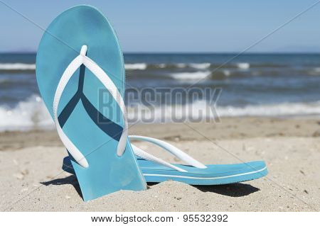 Blue Pair Of Slippers On A Sea Shore With Blue Sea And Sky In Background