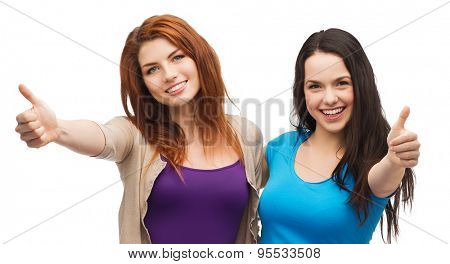 friendship and happy people concept - two smiling girls showing thumbs up