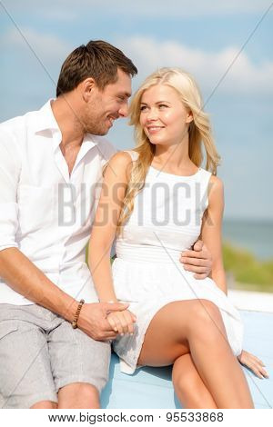 summer holidays and dating concept - smiling couple at sea side