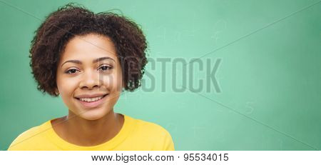 people, race, ethnicity and portrait concept - happy african american young woman face over green chalk board background