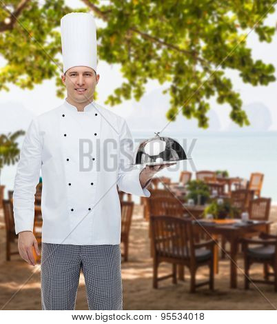 cooking, profession and people concept - happy male chef cook holding cloche over restaurant lounge on beach