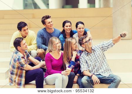 education, friendship, drinks, technology and people concept - group of smiling students with smartphone and paper coffee cup taking selfie at school