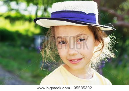 Portrait of smiling beautiful teenage in wide-brimmed hat against green of summer park.