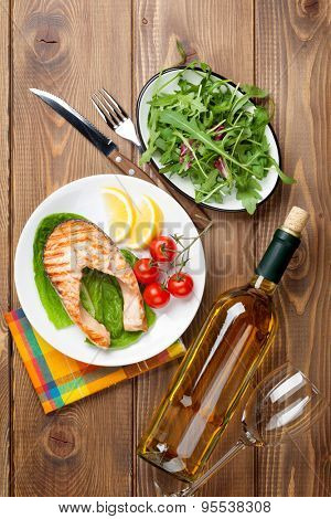 Grilled salmon and white wine on wooden table. Top view