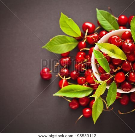 Ripe cherries with green leaves on dark background