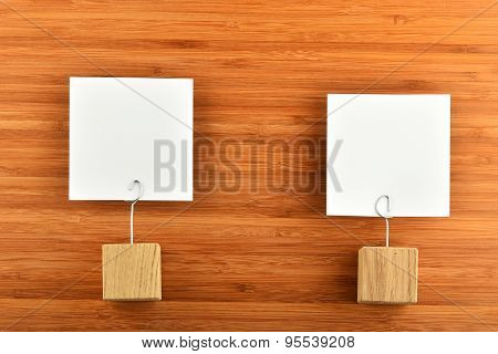 Two Paper Notes With Wooden Holders On Wooden Background