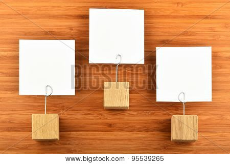 Three Paper Notes With Holders Isolated Bamboo Wooden Background