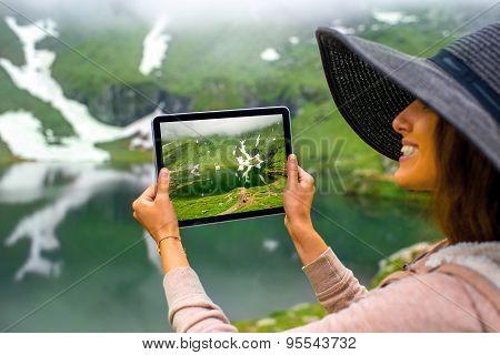 Traveler photographing mountain lake