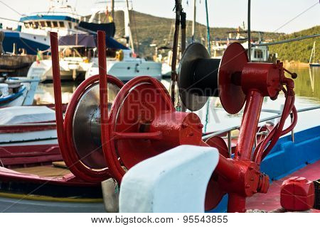 Detail of a fishing boat in a harbor with red colorful machinery