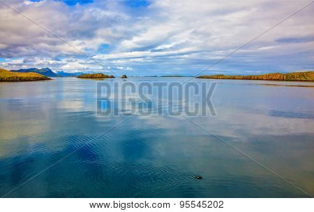 Cold summer in Iceland. Smooth water of the cold fjord reflects clouds