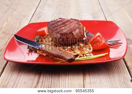 grilled beef fillet medallions on noodles with red hot chili pepper on red plate over wood table